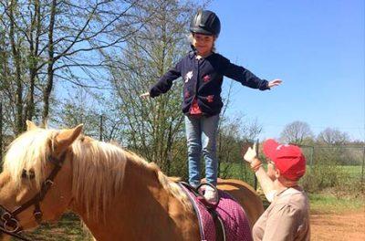 Kind steht auf dem Pferd Gleichgewicht