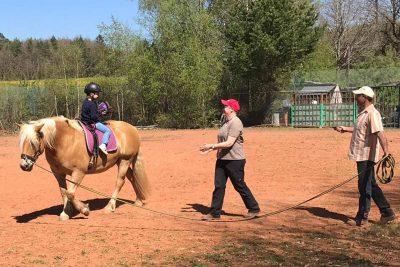 Kind sitzt rückwärts auf dem Pferd